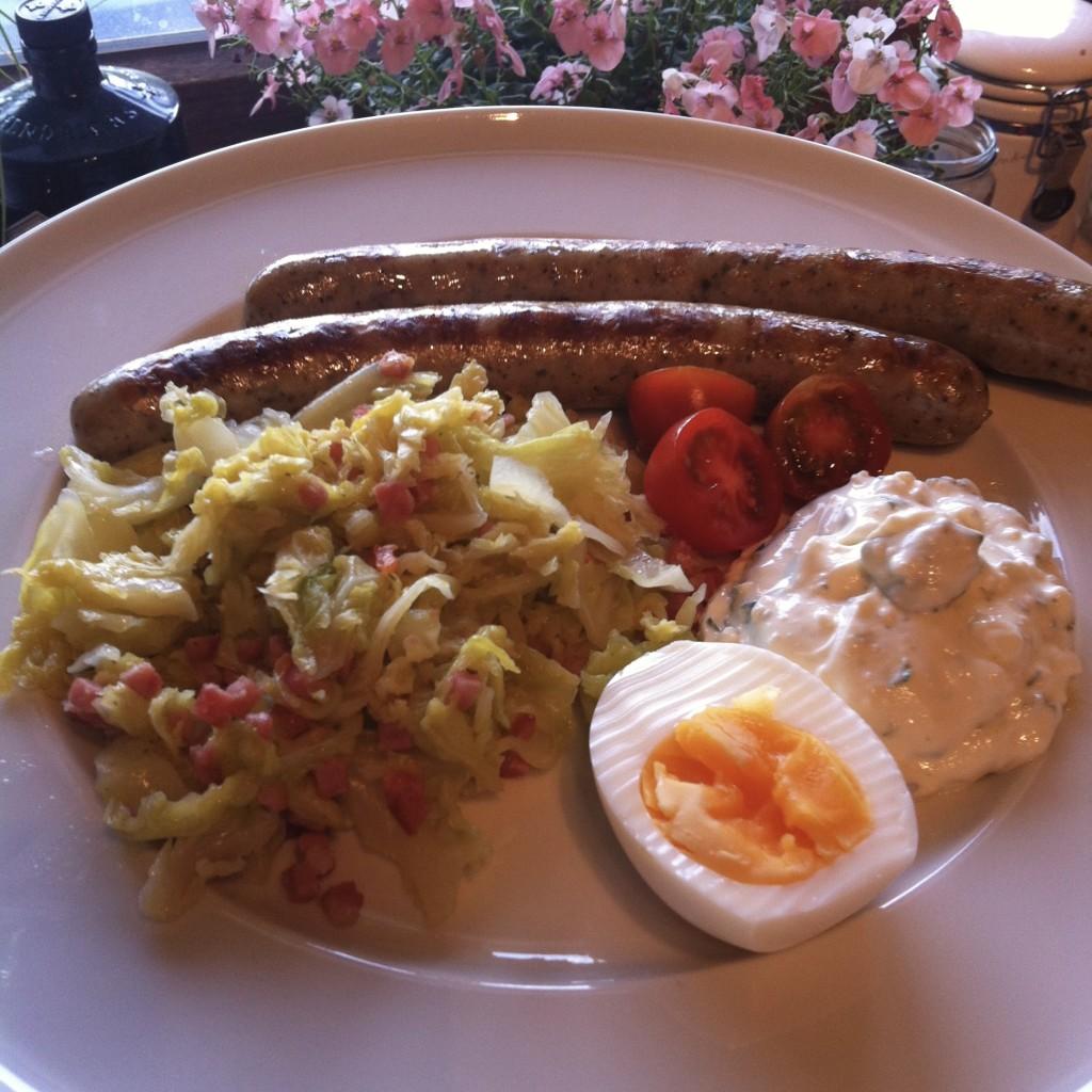 Bratwürstchen, Kohl mit Speck, dazu Ei und Kräuterquark